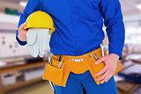 Composite image of handyman holding helmet