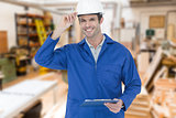 Composite image of happy supervisor wearing hard hat while holding clip board