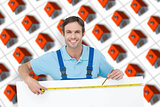 Composite image of happy carpenter measuring blank bill board