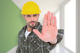 Composite image of confident manual worker gesturing stop sign