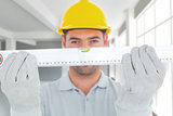 Composite image of portrait of handyman holding spirit level