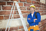 Composite image of thoughtful electrician with arms crossed by ladder