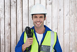 Composite image of confident electrician with wire against white background