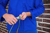 Composite image of electrician cutting wire with pliers