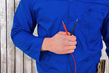 Composite image of electrician holding multimeter
