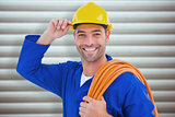 Composite image of confident repairman wearing hard hat while holding wire roll
