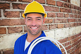 Composite image of electrician carrying wires over white background