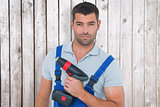 Composite image of portrait of confident carpenter holding power drill