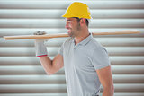 Composite image of worker with plank of wood