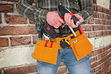 Composite image of manual worker holding gloves and hammer power drill