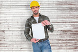 Composite image of smiling manual worker holding clipboard