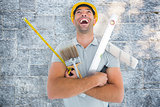 Composite image of laughing manual worker holding various tools