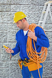 Composite image of electrician reading multimeter in bright office