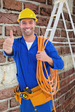 Composite image of male technician with wire roll gesturing thumbs up