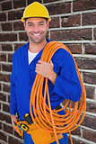 Composite image of smiling handyman with rolled wire on white background