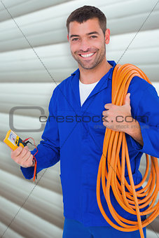 Composite image of smiling electrician with wire roll and multimeter