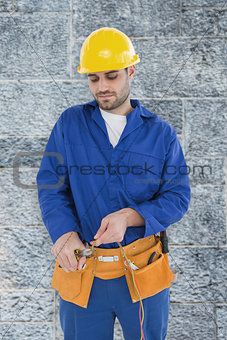 Composite image of male electrician cutting wires