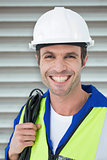 Composite image of happy electrician with wire against white background