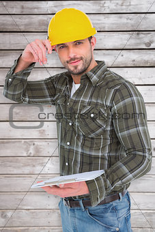 Composite image of smiling handyman writing on clipboard
