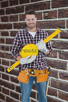 Composite image of handyman holding hard hat and spirit level
