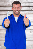 Composite image of smiling mechanic holding spanner while gesturing thumbs up