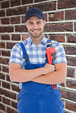 Composite image of confident young male repairman holding adjustable spanner