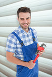 Composite image of confident young male repairman holding monkey wrench