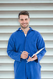 Composite image of smiling male mechanic writing on clipboard