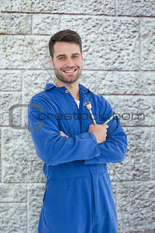 Composite image of smiling young male mechanic holding spanner