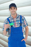 Composite image of confident plumber showing green card