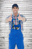 Composite image of confident plumber showing thumbs up sign