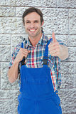 Composite image of confident plumber holding tool while gesturing thumbs up