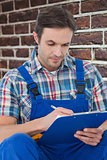 Composite image of plumber writing notes on clipboard