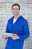 Composite image of handsome mechanic holding digital tablet