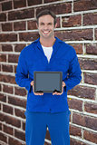 Composite image of happy mechanic holding digital tablet