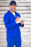 Composite image of portrait of happy male mechanic writing on clipboard