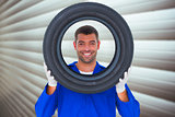 Composite image of happy mechanic looking through tire