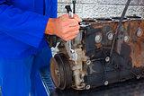 Composite image of male mechanic repairing car engine