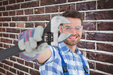 Composite image of handyman wearing protective glasses while holding wrench