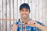Composite image of portrait of happy plumber fixing pipe