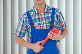 Composite image of cropped image of plumber holding monkey wrench