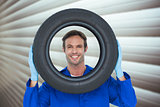 Composite image of confident mechanic looking through tire