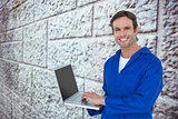 Composite image of handsome mechanic using laptop over white background