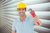 Composite image of happy carpenter holding monkey wrench