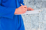 Composite image of male mechanic writing on clipboard