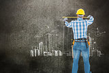 Composite image of rear view of construction worker using measure tape
