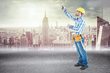 Composite image of construction worker using measure tape