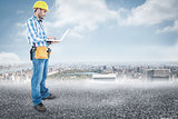 Composite image of full length of repairman using laptop