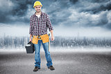 Composite image of happy male hanyman carrying toolbox