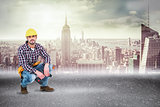 Composite image of crouching handyman holding power drill